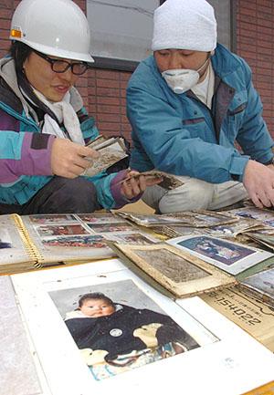 灾区志愿者为灾民寻回丢失的相册和照片